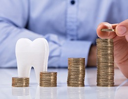 Cost of dental emergencies in Ann Arbor represented by coins and tooth
