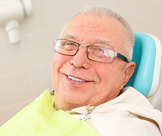 Smiling senior man in dental chair after full mouth reconstruction
