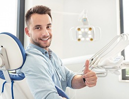 man giving thumbs up in the dental chair
