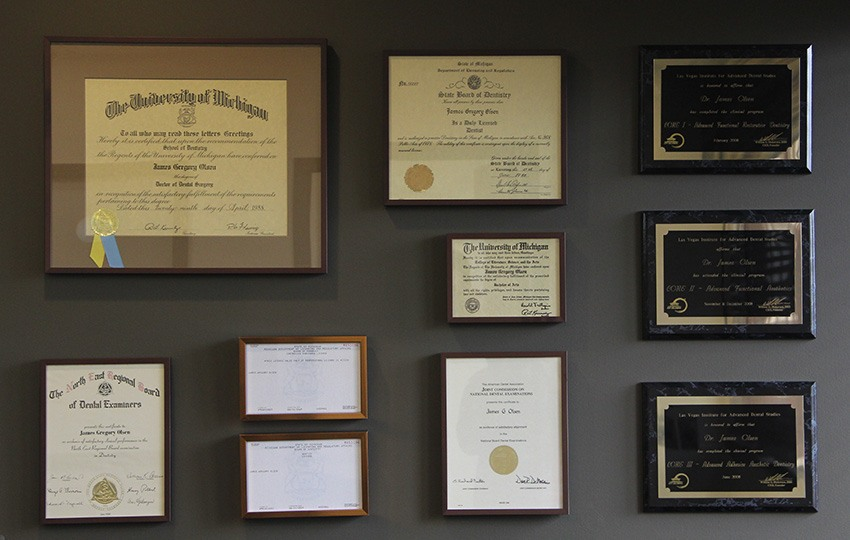 Wall of James Olsen's dental certificates and awards