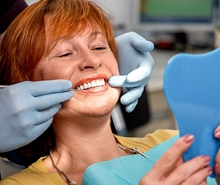 Senior woman and dentist looking at smile in mirror