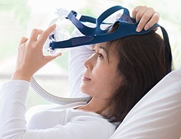 Woman placing her CPAP mask