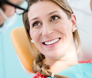 Woman in dental chair discussing dental bridge tooth replacement
