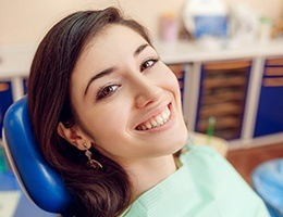 Smiling woman in dental chair after porcelain veneer treatment
