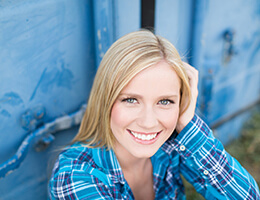 A young woman with blonde hair and a blue, plaid shirt smiles after receiving her veneers